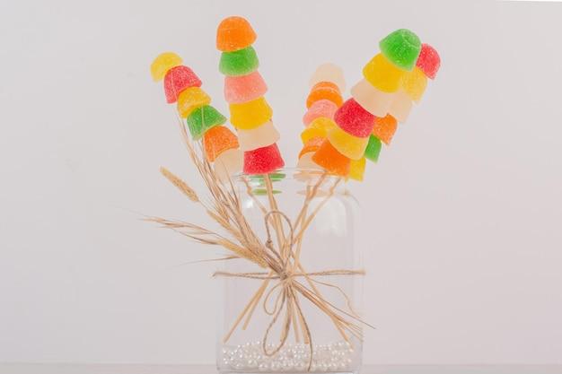 Bâtonnets de confitures colorées dans un bocal en verre.
