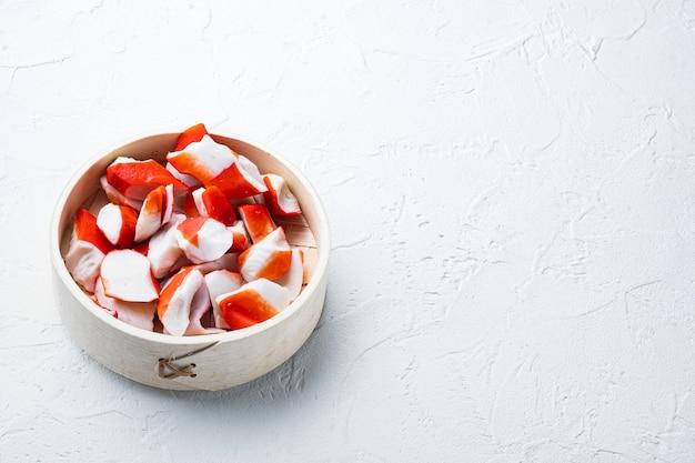 Bâtonnets de crabe aux fruits de mer hachis de poisson semi-fini avec un ensemble de crabe bleu nageant, sur un plateau en bois, sur fond blanc, avec fond et espace pour le texte