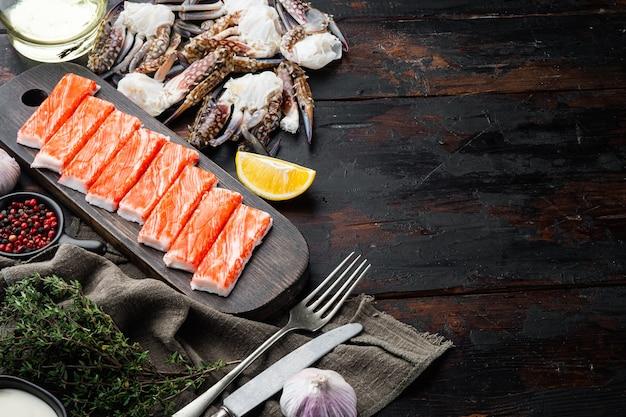 Bâtonnets de crabe aux fruits de mer hachis de poisson semi-fini avec un ensemble de crabe de natation bleu, sur fond de bois foncé, vue de dessus à plat, avec fond et espace pour le texte