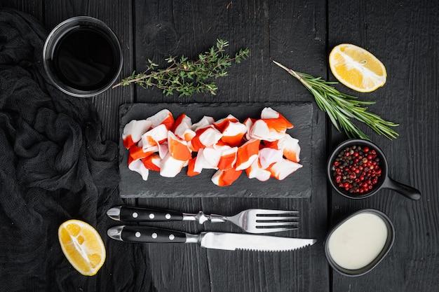 Bâtonnets de crabe aux fruits de mer hachis de poisson semi-fini avec un ensemble de crabes bleus, sur fond de table en bois noir, vue de dessus à plat