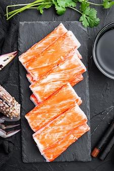 Bâtonnets de crabe aux fruits de mer hachis de poisson semi-fini avec un ensemble de crabes bleus, sur planche de pierre, sur fond noir, vue de dessus à plat