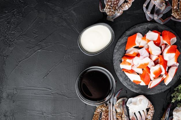 Bâtonnets de crabe poisson semi-fini haché de fruits de mer avec jeu de crabe bleu natation, sur fond noir, vue de dessus à plat, avec copyspace et espace pour le texte