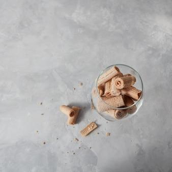 Bâtonnets crémeux wafer dans une tasse en verre un sur un fond de pierre grise avec espace de copie. vue de dessus.