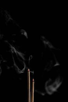Bâtonnets d'encens et fumée de bâton d'encens sur fond noir