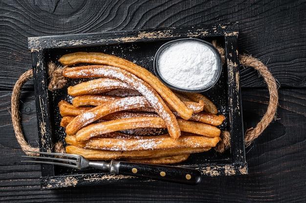 Bâtonnets frits de churros avec du sucre en poudre dans un plateau en bois. fond noir. vue de dessus.