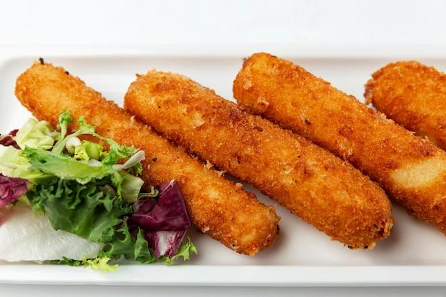 Bâtonnets de fromage frit avec des feuilles de salade verte fraîche. collation appétissante. fermer. fond blanc.