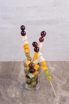 Bâtonnets de fruits mélangés en verre sur table en marbre.