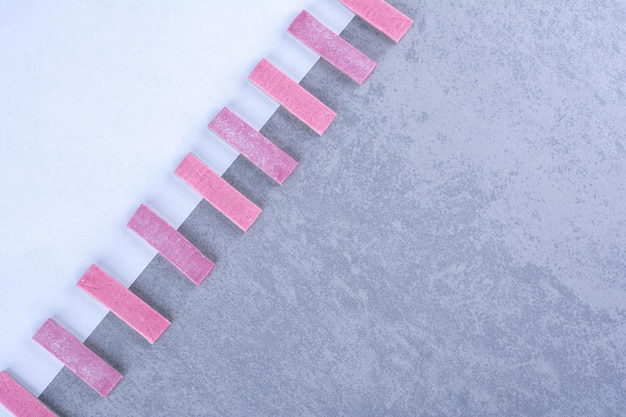 Bâtonnets de gomme violets alignés en diagonale le long de la bordure d'une feuille de papier sur une surface en marbre