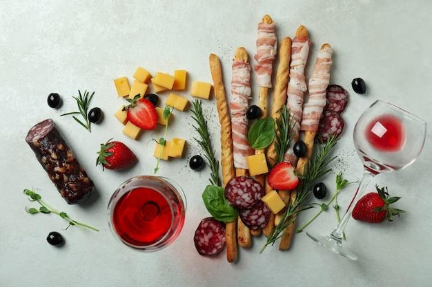 Bâtonnets de grissini avec du bacon, des collations et du vin sur fond texturé blanc