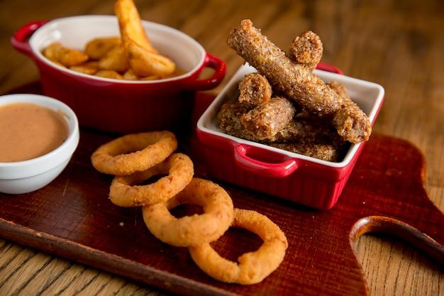 Bâtonnets, oignons frits et tomates frites avec sauce