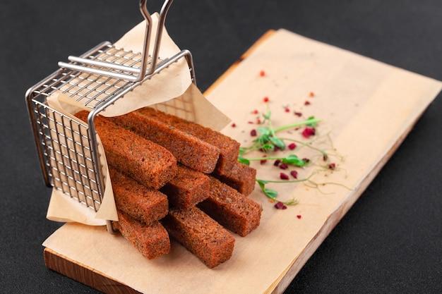 Bâtonnets de pain noir frits chauds, dispersés dans la grille