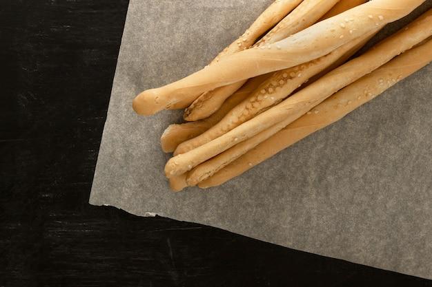 Des bâtonnets de pain se trouvent sur du papier sulfurisé