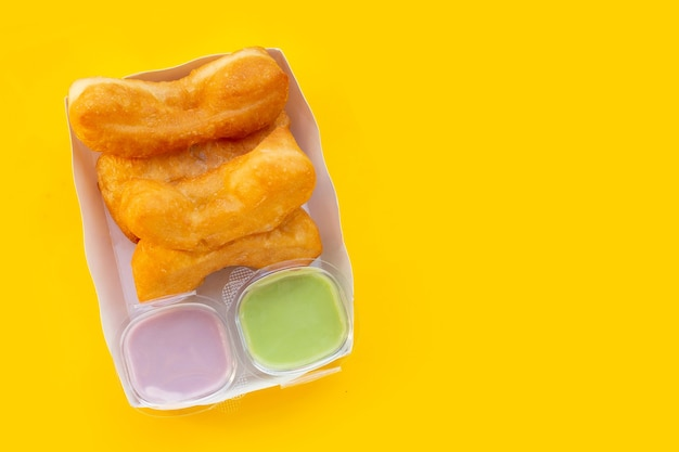 Bâtonnets de pâte frits ou bâtonnets de pain chinois sur fond jaune.