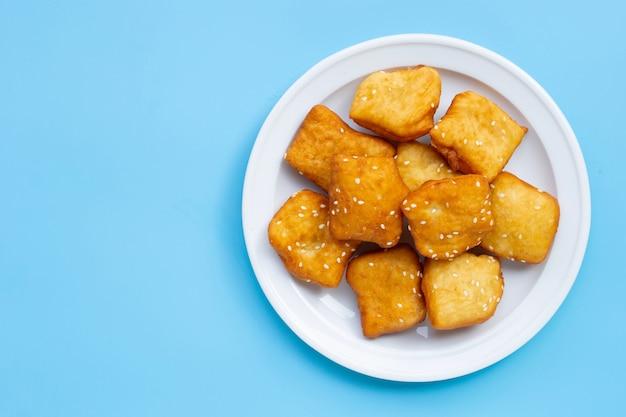 Bâtonnets de pâte frits chinois avec des graines de sésame blanc sur fond bleu.