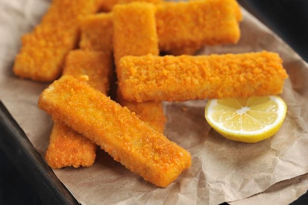 Bâtonnets de poisson panés frits et citron sur papier