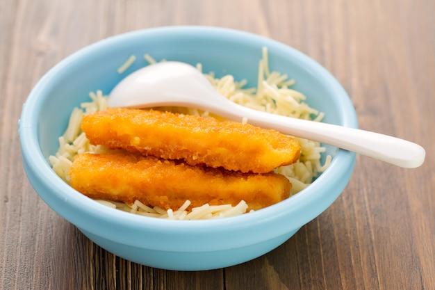 Bâtonnets de poisson avec des pâtes dans un bol bleu sur un fond en bois marron