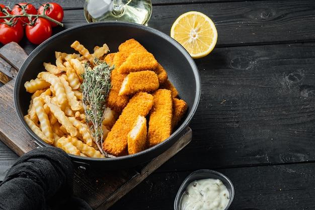 Bâtonnets de poisson avec pommes de terre frites, sur poêle en fer à frire, sur fond de table en bois noir, avec fond et espace pour le texte