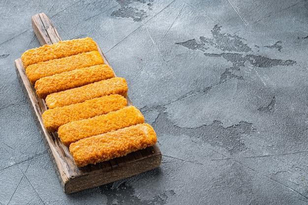 Bâtonnets de poisson surgelés. aliments pour poissons biologiques sur une planche à découper en bois sur fond gris