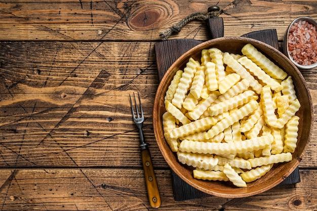 Bâtonnets de pommes de terre frites au four ondulé congelé dans une assiette en bois