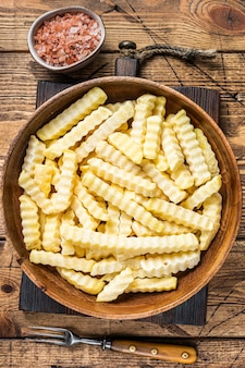 Bâtonnets de pommes de terre frites au four ondulé surgelé dans une assiette en bois. fond en bois. vue de dessus.