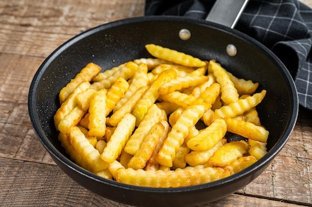 Bâtonnets de pommes de terre frites crinkle frites dans une poêle