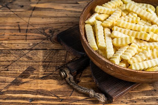 Bâtonnets de pommes de terre frites surgelées au four crinkle dans une assiette en bois.