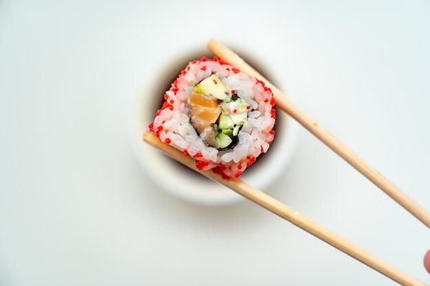 Les bâtonnets de sushi gardent le rouleau avec une tasse de sauce soja sur fond blanc
