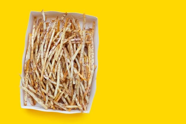 Bâtonnets de taro frits dans une boîte en papier sur fond jaune.
