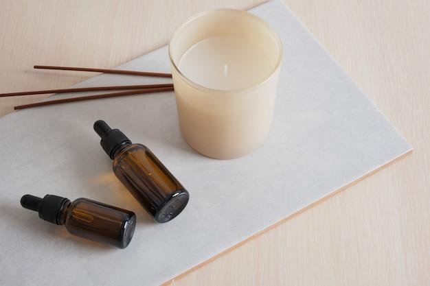 Bâtons d'arôme, bouteille en verre marron avec pipette et bougie aromatique sur carreaux de céramique, sérum ou huile cosmétiques naturels pour les soins de la peau du corps