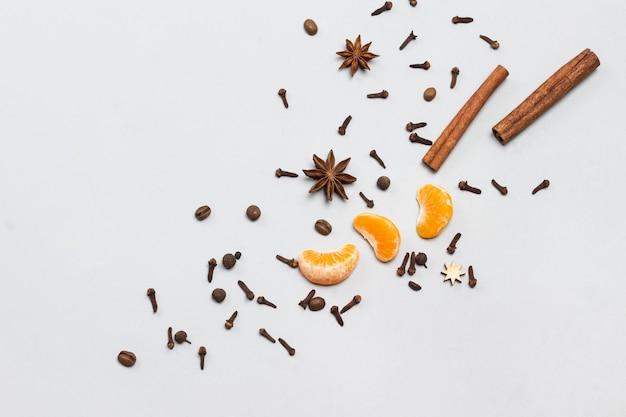 Des bâtons de cannelle et de l'anis étoilé, des clous de girofle aux épices, des tranches de mandarine sont dispersés sur la table. mise à plat. copiez l'espace.