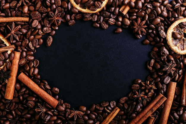 Bâtons de cannelle, anis étoilé, grains de café et orange séchée sur la table de la cuisine