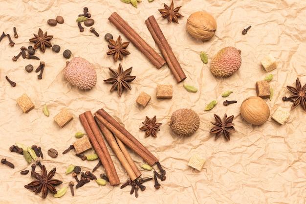 Bâtons de cannelle, anis étoilé, piment de la jamaïque et cardamome, litchi et noix. fond de papier brun. mise à plat