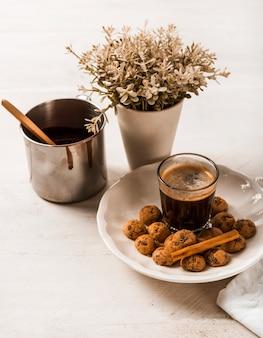 Bâtons de cannelle sur des biscuits au chocolat avec verre à café et vase
