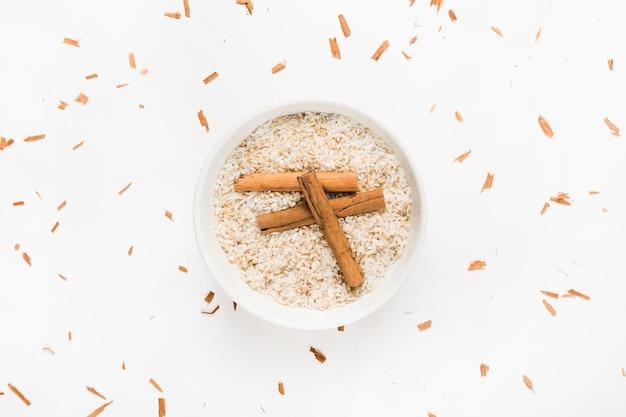 Bâtons de cannelle sur un bol de riz non cuit sur fond blanc