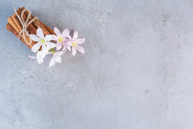 Bâtons de cannelle en corde avec des fleurs blanches et roses sur fond gris.