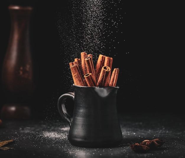 Bâtons de cannelle dans une tasse noire