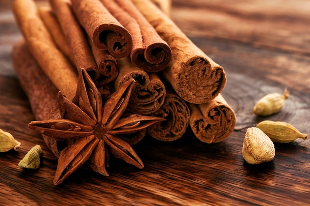 Bâtons de cannelle, étoiles d'anis et cardamome sur une table en bois. ensemble d'épices pour vin chaud, gâteau de noël, biscuits. mise au point sélective. fermer