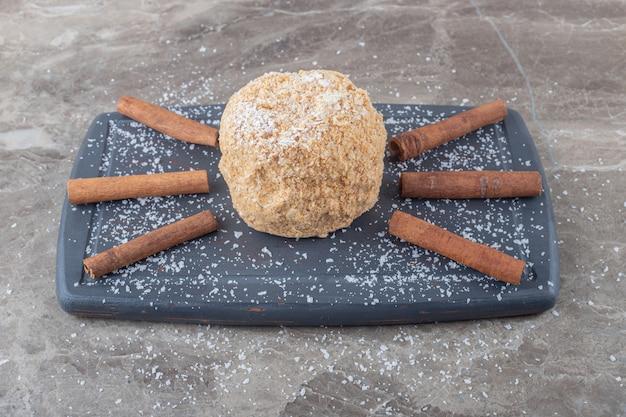 Bâtons de cannelle et un gâteau d'écureuil sur une planche sur une surface en marbre