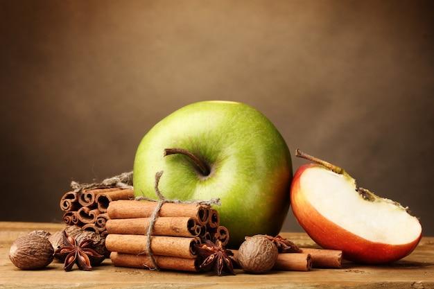 Bâtons de cannelle, pomme muscade et anis sur table en bois sur fond marron