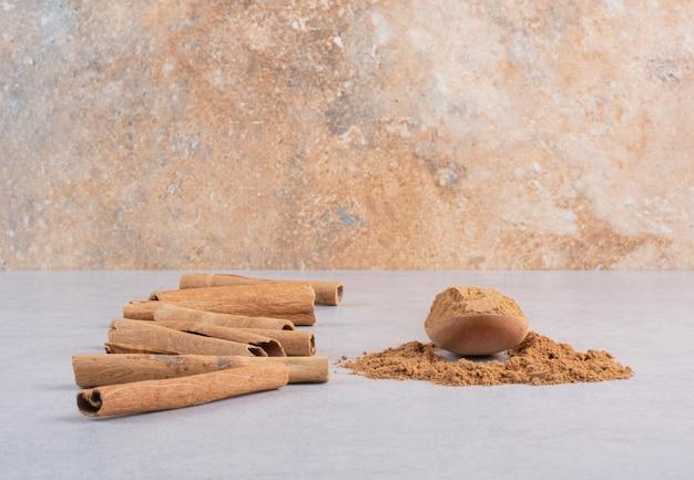 Bâtons de cannelle avec de la poudre sur fond de béton.