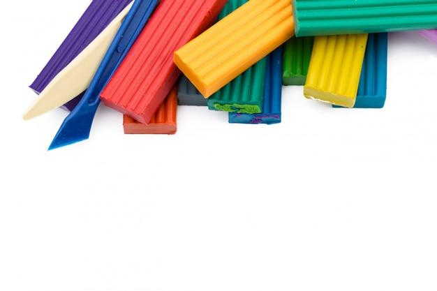 Bâtons colorés de pâte à modeler isolés sur blanc
