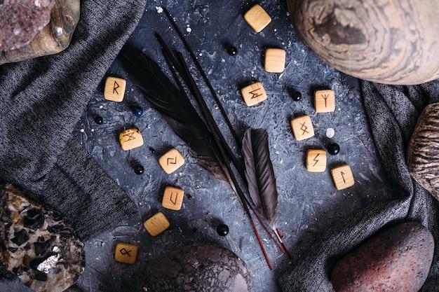 Bâtons d'encens parmi les pierres runiques d'attirail sombre et ésotérique