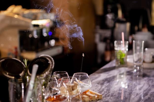Bâtons de fumée aromatique sur comptoir de bar.