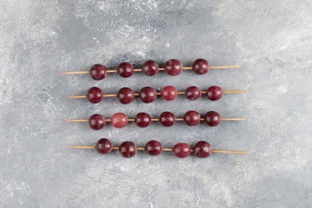 Bâtons de raisin rouge frais placés sur fond de marbre.