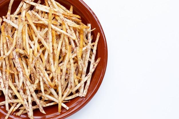 Bâtons de taro frits dans un bol sur fond blanc.