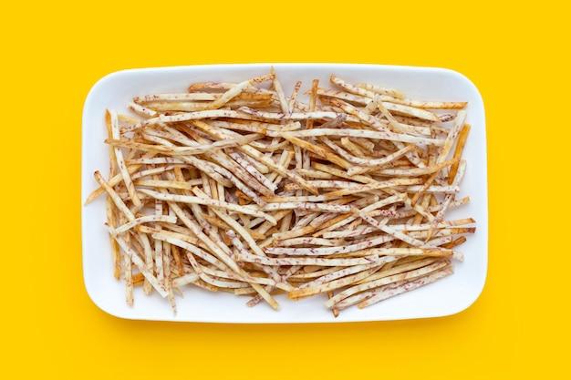 Bâtons de taro frits en plaque blanche sur fond jaune.