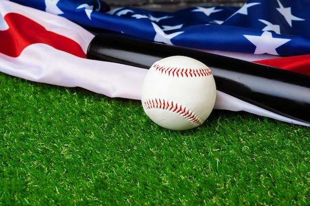 Batte de baseball et balle avec drapeau américain sur l'herbe