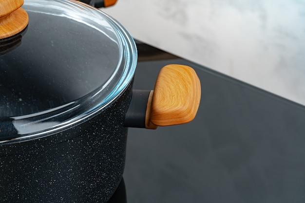 Batterie de cuisine noire sur cuisinière à induction contre le mur gris