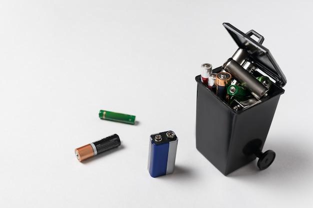 Batteries usagées dans la poubelle sur blanc concept de déchets électroniques. élimination écologique.