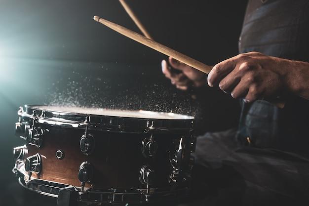 Le batteur à l'aide de baguettes frappant la caisse claire avec des éclaboussures d'eau sur fond noir sous l'éclairage de studio se bouchent.